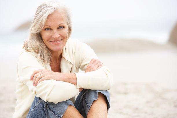 woman smiling sitting on beach