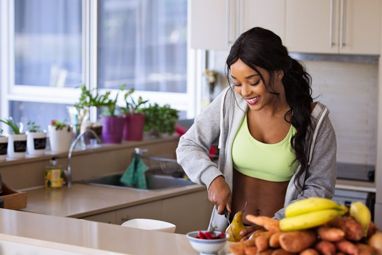 woman in exercise clothes cutting food