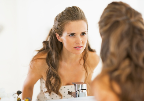 woman looking at mirror concerned